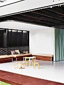 Blick von einem Innenhof durch geöffnete Glasschiebetüren in sparsam möblierten Wohnraum mit Kindertisch-Klassiker von Alvar Aalto