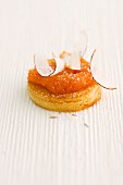 A round slice of bread topped with carrot and passion fruit spread and grated coconut