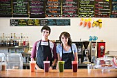 A young woman and a young man in a cafe with smoothies on the counter
