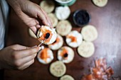 Blinis being topped with salmon and caviar