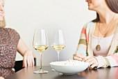 Zwei Frauen mit Popcorn und Weingläsern beim Esstisch