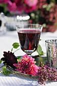 Dahlienblüte vor Rotweinglas und Callicarpa auf Silbertablett