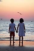 Junge und Mädchen Hand in Hand am Meeresufer in Abendstimmung