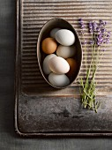 Eggs in metal bowl next to lavender