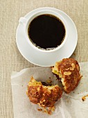 A cup of coffee and an almond croissant