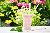 Three pink spotted paper cups and matching straws on a garden table