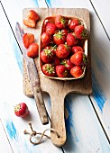 Fresh strawberries in a wooden basket on a chopping board with a knife