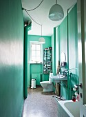 Blick durch offene Tür in mintgrün getöntes, schmales Altbau-Bad mit weißen Hängeleuchten