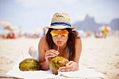 Kokosnußsaft schlürfende junge Frau
