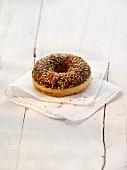 A doughnut with chocolate glaze and colourful sugar sprinkles