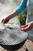 A fish being grilled in a fish basket