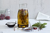 Homemade herb oil in a glass bottle surrounded by ingredients