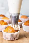 Muffin mit Buttercreme aus einem Spritzbeutel verzieren