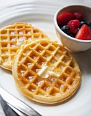 Waffles with butter, maple syrup and berries