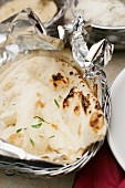 Naan bread in tin foil in a breadbasket