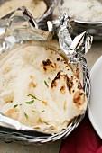 Naan bread in tin foil in a breadbasket