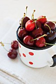 Cherries in an enamel mug with red dots