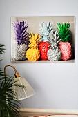 Abbildung quietschbunt lackierter Ananasfrüchte an lichtgrauer Wand, Vintage-Leuchte und Palmenblätter im Vordergrund