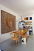 Grossformatiges Aborigines-Kunstwerk hinter Esstisch mit Bugholzstühlen, bunt bestücktes Küchenregal im Hintergrund