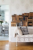 Vintage Sitzbank mit weißem Metallgestell und Spitzendecke, vor halbhoher Ablage mit antiquarischen Bücherstapeln, seitlich offener Durchgang und Blick ins Esszimmer