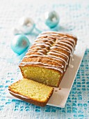 Lemon cake drizzled with icing sugar, sliced