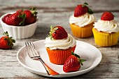 Strawberry cupcakes topped with cream