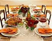Roast turkey and cranberries on a table laid with autumnal decorations