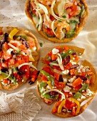 Mini pizzas with peppers, olives and feta (seen from above)