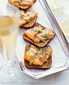 Slices of bread topped with smoked salmon and a dill sauce
