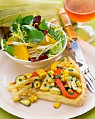 A slice of vegetable tart with salad
