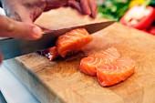 Roher Lachs wird in Stücke geschnitten