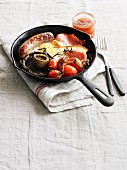 And English breakfast featuring bacon, sausage, fried egg, Portobello mushrooms and tomatoes in a pan