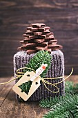 A Christmas gift wrapped in knitted gift wrap with a Christmas tree made of chocolate biscuits