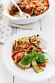 Courgette and tomato gratin in a baking dish and on a plate