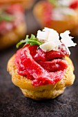 A profiterole with beef carpaccio, rocket and grated Parmesan