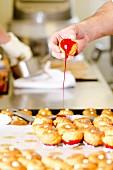 Konditor taucht Windbeutel in rote Karamellsauce (Vorbereitung für die Hochzeitstorte Piece Montee aus Frankreich)
