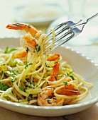 Linguine with prawns and herbs on a fork
