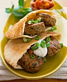 Meatballs in pita bread with spring onions and sour cream
