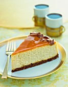 A slice of cake with caramel glaze and chocolate curls