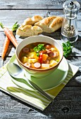 Vegetable soup with sausage in soup bowl