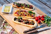 Pizza baguettes with ham, salami, mozzarella, tomato, rocket, sweetcorn and olives