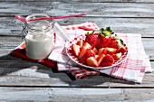 A jar of natural yoghurt and a plate of strawberries on tea towels on a wooden table