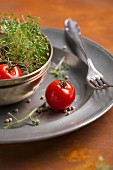 Tomatoes, garden cress and peppercorns in a bowl on a tin plate