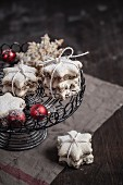Cinnamon stars decorated with icing sugar with red Christmas baubles on a cake stand
