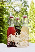 Three glass bottles of homemade syrup on a garden table: rhubarb syrup, cherry syrup and elderflower syrup