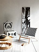Stoffbespannter, moderner Holzsessel mit grafischem und Polsterstuhl mit floralem Muster vor Baumstammfoto, im Vordergrund ein Geflechttisch