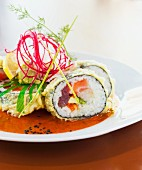 Maki sushi with tuna, spring onions and avocado in a spicy sauce
