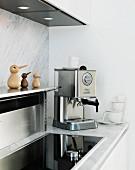 weiße Küche mit Marmor Rückwand und Arbeitsfläche - Edelstahl-Ablage, integriertes Kochfeld und Espressomaschine