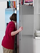 A woman looking in a fridge