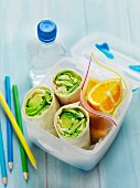 A healthy lunch for school with wraps, fruit and water